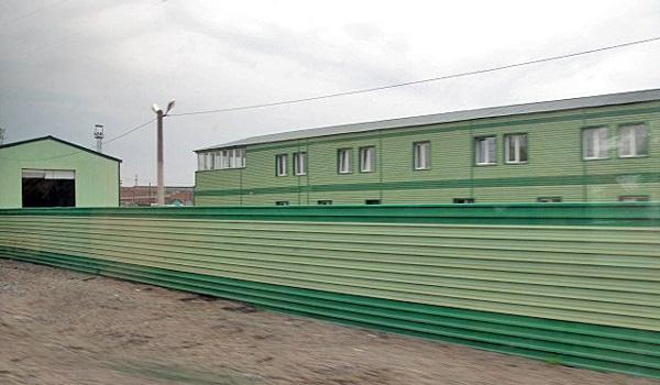 Grün angestrichene Zäune und Gebäude am Rande einer Bahnlinie in Rußland