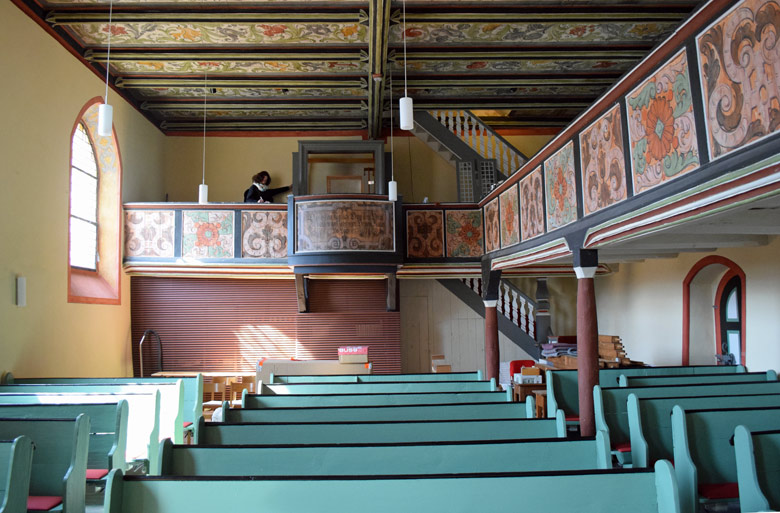 Innenansicht der Kirche St. Briccius in Bad Belzig im Landkreis Potsdam-Mittelmark in Brandenburg mit grünen Kirchenbänken, bemalten Holzpaneelen und einer in der Restaurierung befindlichen Orgel