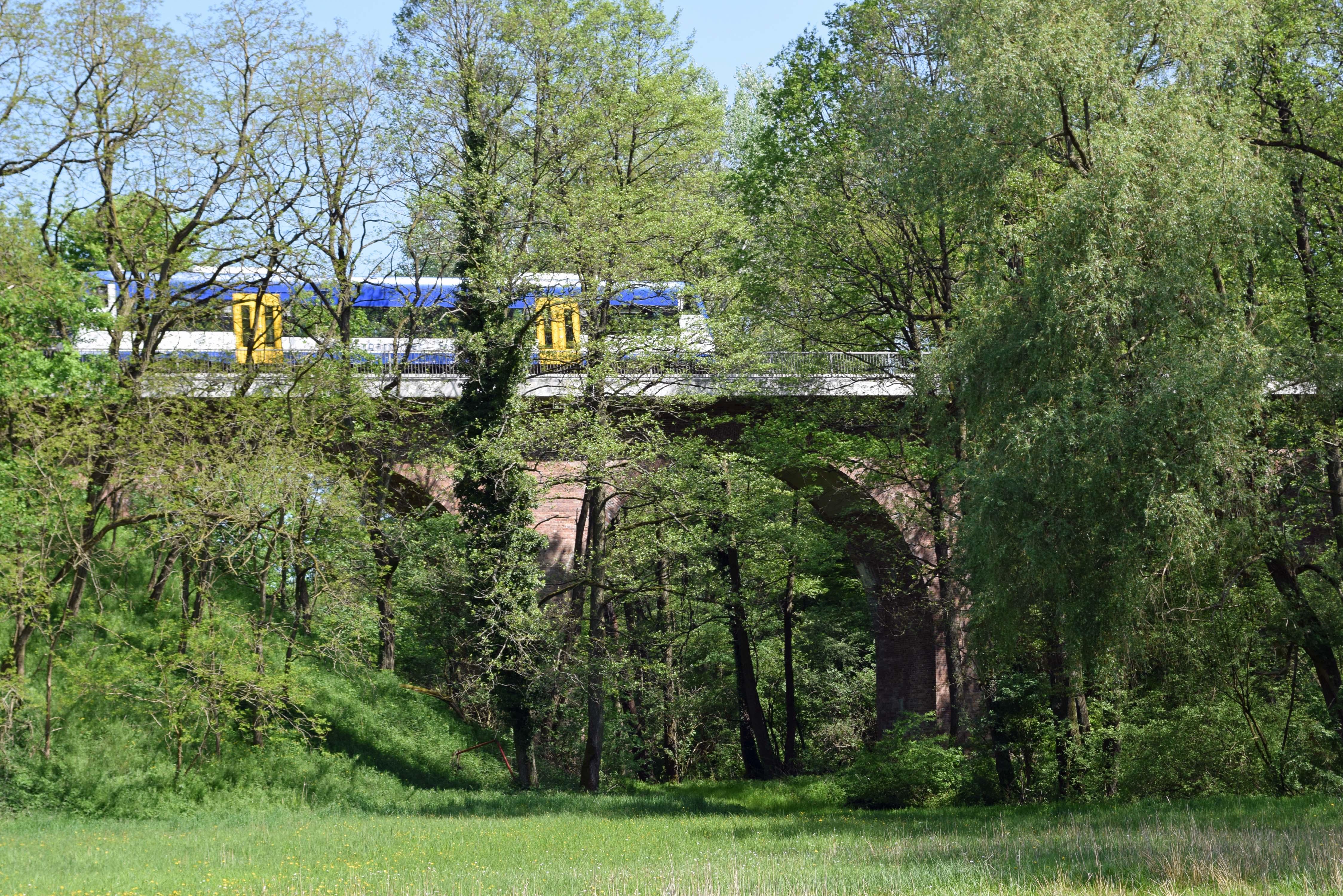 Eisenbahnviadukt bei Lindenberg in der Nähe von Beeskow in Brandenburg mit einem blau-gelben Triebwagen bei der Überfahrt