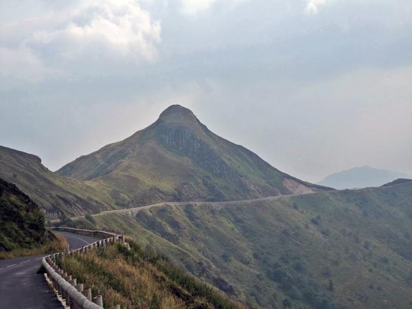 Abfahrt vom Puy Mary in Zentralfrankreich mit einer Kurvenstrecke und erloschenen Vulkanen
