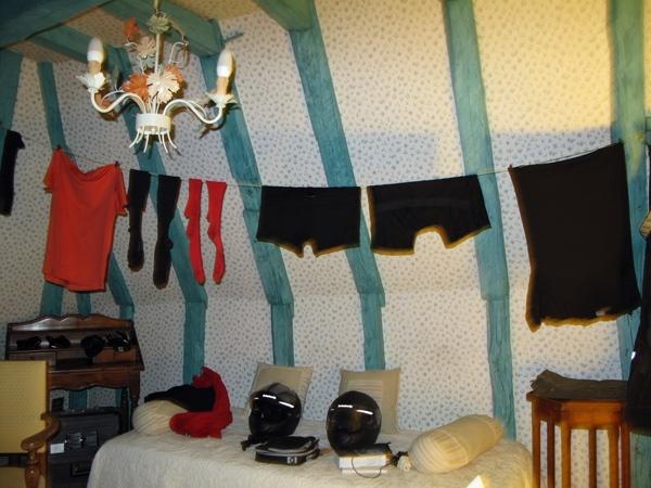 Gewaschene Wäsche im Hotelzimmer auf einer aufgespannten Wäscheleine und aufgehängten Hemden, Strümpfen und Hosen und zwei Motorradhelmen auf dem Bett