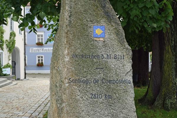Granitstein mit Wegweisungn nach Santiago de Compostela vor der Wallfahrtskirche von Neunkirchen b. Hl. Blut im Bayerischen Wald