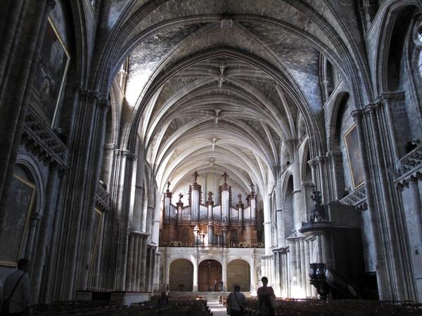 Innenraum der Kathedrale von Bordeaux mit gotischen Kreuzrippengewölben und einer Orgel an der Stirnseite des Kirchenschiffs