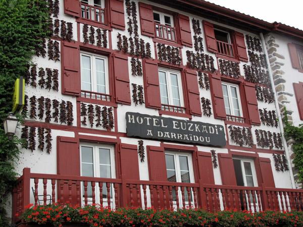 Haus im baskischen Stil in Espelette mit Chilischoten, roten Fensterläden und Balkongeländern, gesehen auf einer Motorradtour Südwestfrankreich Teil 2