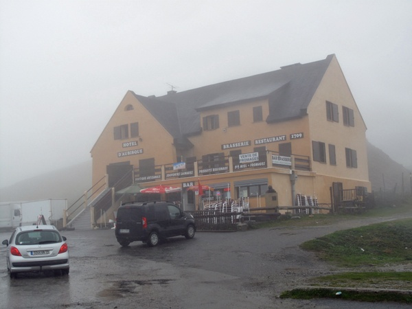 Passhöhe des Col d'Aubisque in den französischen Pyrenäen im dichten Nebel mit einem Restaurant und zwei Autos davor bei einer Motorradtour Südwestfrankreich Teil 2
