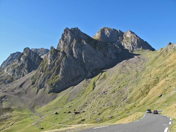 Passstrasse des Col du Tourmalet in den französischen Pyrenäen mit zwei Autos vor der Bergkulisse bei einer Motorradtour Südwestfrankreich Teil 2