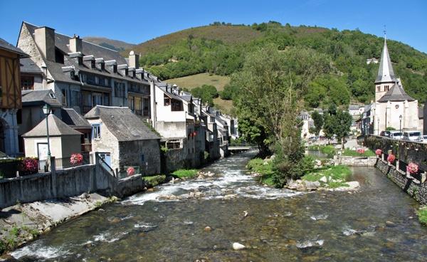 Flusspanorama von Arreau in den französischen Pyrenäen mit alten Steinhäusern an beiden Ufern, Blumenschmuck und einer Kirche