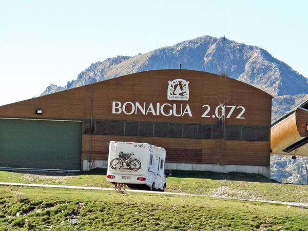 Passhöhe des Port de la Bonaigua in Katalonien mit einer Holzhalle und der Aufschrift Bonaigua 2.072, einem Wohnmobil und dem Pyrenäenmassiv im Hintergrund