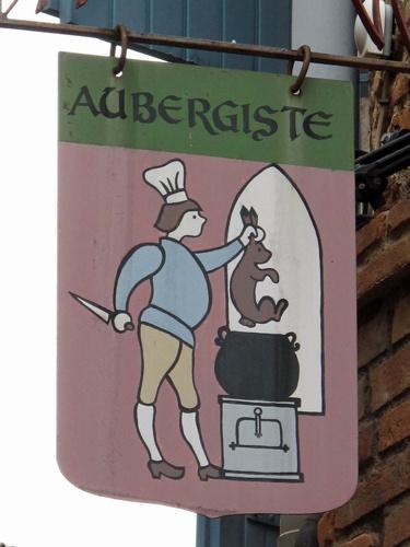 Hotel Aubergiste Albi (Département Tarn, Südwesrfrankreich) mit einem Schild, auf dem ein Koch mit Messer einen Hasen in einen Topf steckt