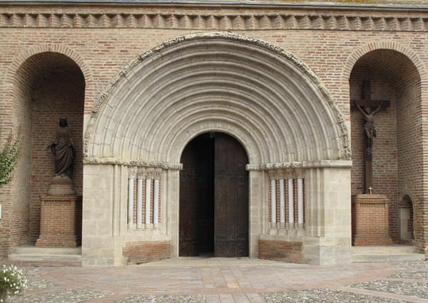 Hauptportal Eglise Notre-Dame-du-Bourg Rabastens im Département Tarn mit zwei Seitenbögen, in denen ein Kruzifix und eine Madonnenstatue stehen