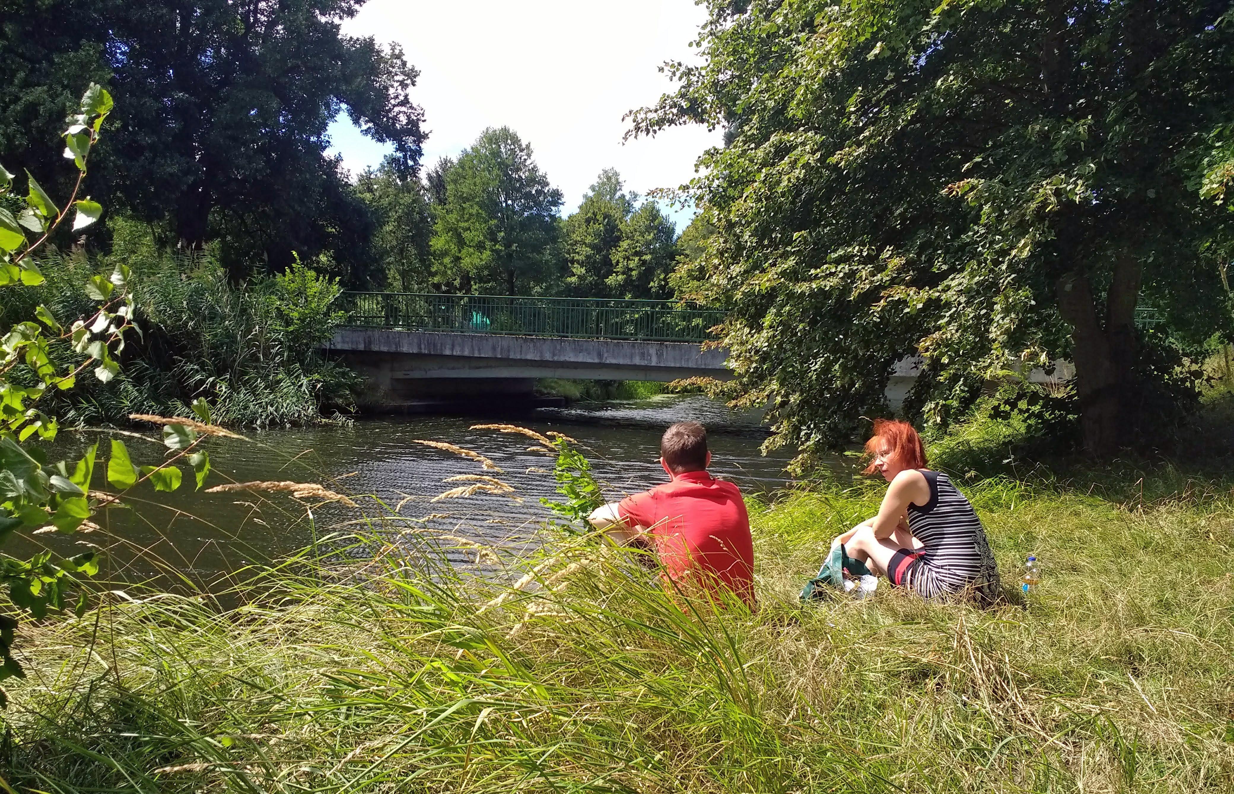 Einer der lauschigen Picknickplätze: Rothaarige Motorradfahrerin und ein junger Mann im roten T-Shirt beim Picknick an einer Brücke am baumbestandenen Flussufer