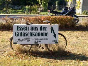 Schild vor einem alten Fahrrad mit der Aufschrift Essen aus der Gulaschkanone
