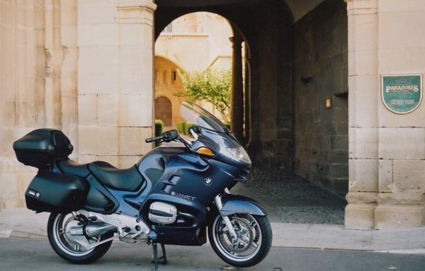 Motorradtour planen: Bepacktes blaues Motorrad BMW R 1150 RT vor Parador in Spanien mit Durchblick durch das Tor in den Innenhof