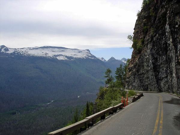 Bergstrasse auf dem Logan Pass in Montana mit steiler Felswand rechts und Blick ins Tal links