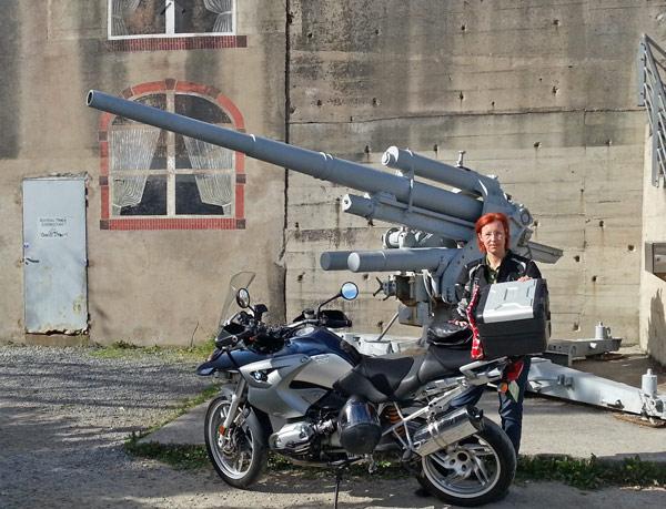 Motorrad BMW R 1200 GS mit einer mit Flak 8,8-cm und einer rothaarigen Motorradfahrerin vor einem Atlantikwallbunker