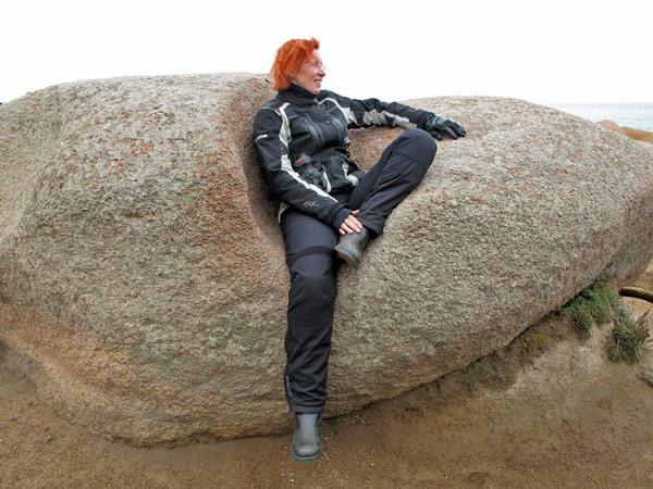 Rothaarige Motorradfahrerin in einer schwarzen Kombi auf rosa Felsen in der Bretagne