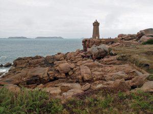 Bild vom Leuchtturm von Perros-Guirec an der bretonischen Atlantikküste mit roten Felsen im Vordergrund