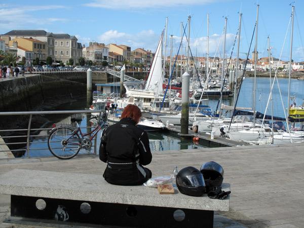 Rothaarige Motorradfahrerin in schwarzer Kombi auf einer Steinbank im Hafen von Les Sables d'Olonne an der französischen Atlantikküste