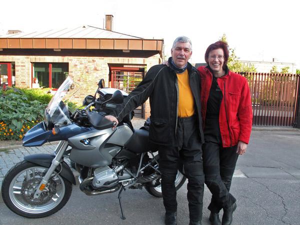 Motorradfahrer mit rothaariger Motorradfahrerin und einer BMW R 1200 GS beim Aufbruch zur Tour