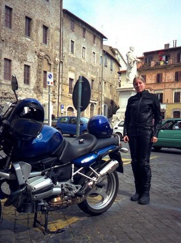 Motorradpause in Palestrina mit blauer BMW R 1100 R und einer blonden Motorradfahrerin. Im Hintergrund das Denkmal des Komponisten bei einer Tour auf Motorrad-Traumstrassen in den Abruzzen
