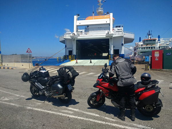 Zwei Motorräder vor einer Fähre vor der Überfahrt über die Straße von Messina bei einer Motorradtour nach Süditalien