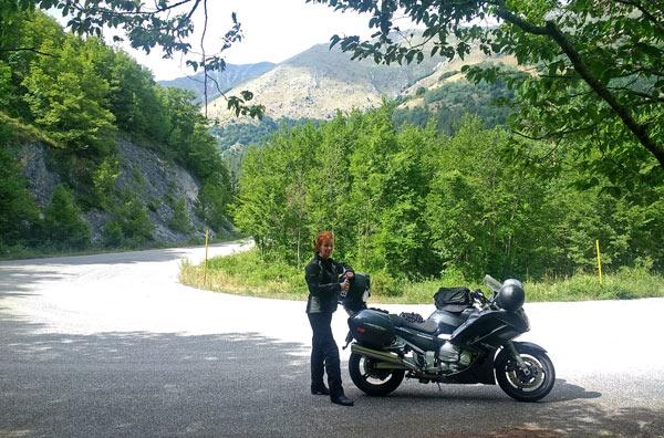 Rothaarige Motorradfahrerin am Gran Sasso bei einer Motorradtour nach Süditalien