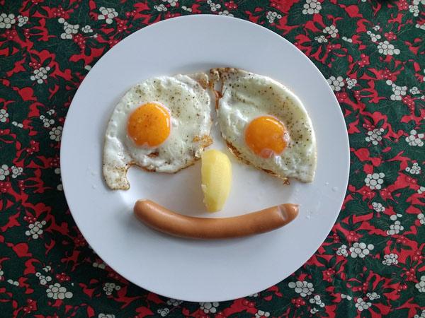 Spiegeleier mit Würstchen und Kartoffel als Gesicht dekoriert