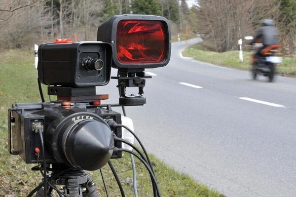 Radarblitzer am Strassenrand mit Motorrad in der Kurve