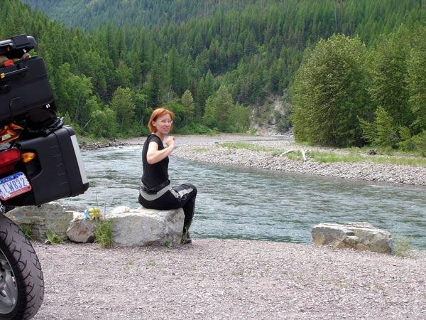 rothaarige motorradfahrerin mit bmw r 1200 gs bei der rast am flathead river in montana