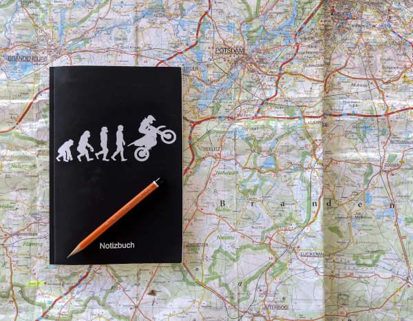 neue ziele fuer motorradtouren: notizbuch auf landkarte