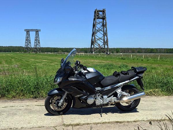 motorrad vor den hoelzernen antennenmasten in brueck brandenburg