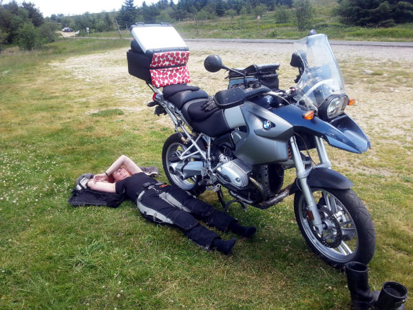 langstreckenkomfort auf dem motorrad: ermuedete motorradfahrerin neben bmw r 1200 gs