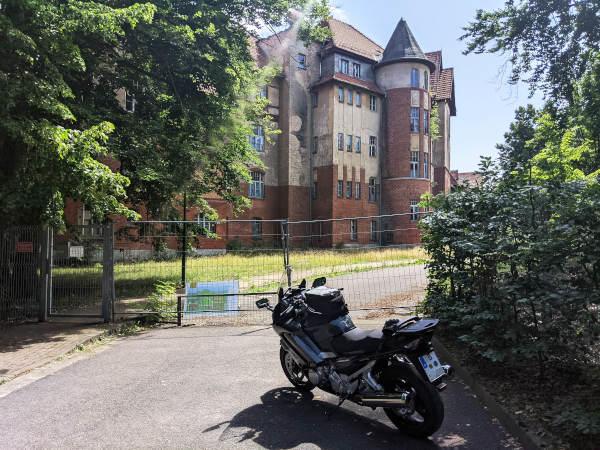eingang zum verfallenen sanatorium in hohenlychen mit motorrad